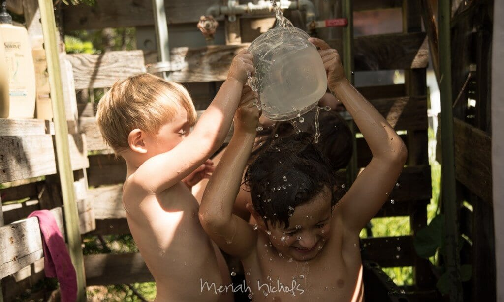 3 kids in a contractor tote- bathtub, with  a shower made of pallets around them. One boy is dumping water over the other boy's head; the water droplets are visible