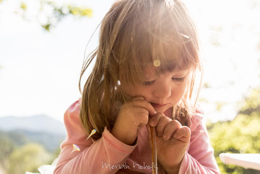 a small girl - Moxie - with light brown/dark blonde hair focuses on her honey stick (literally, a plastic bag shaped like a stick that is filled with honey)
