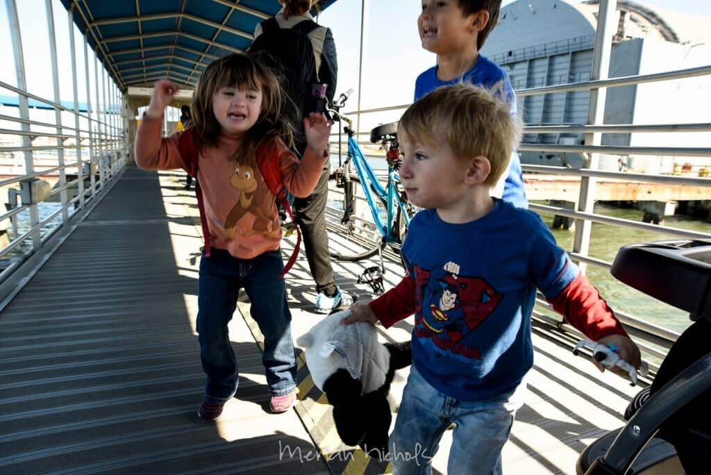 three exuberant children gleefully jump and smile in anticipation as they see the ferry approach (- not shown: the line is full of people on their iphones)