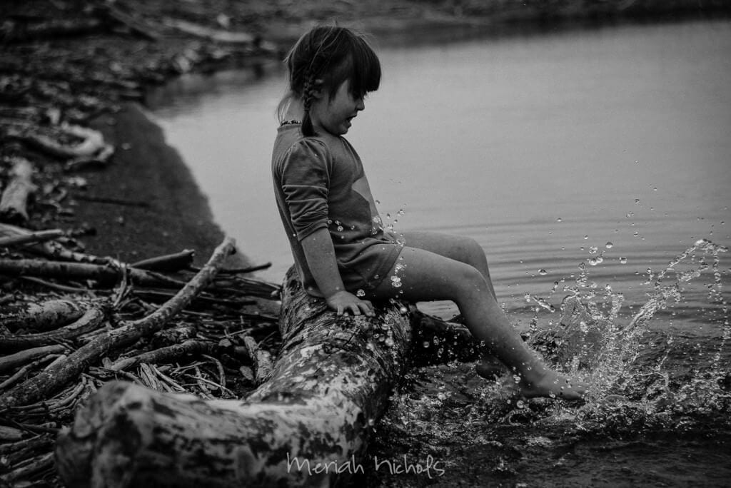 little girl kicking her feet in water