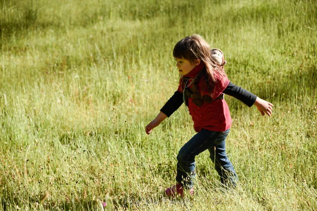 child striding through meadow