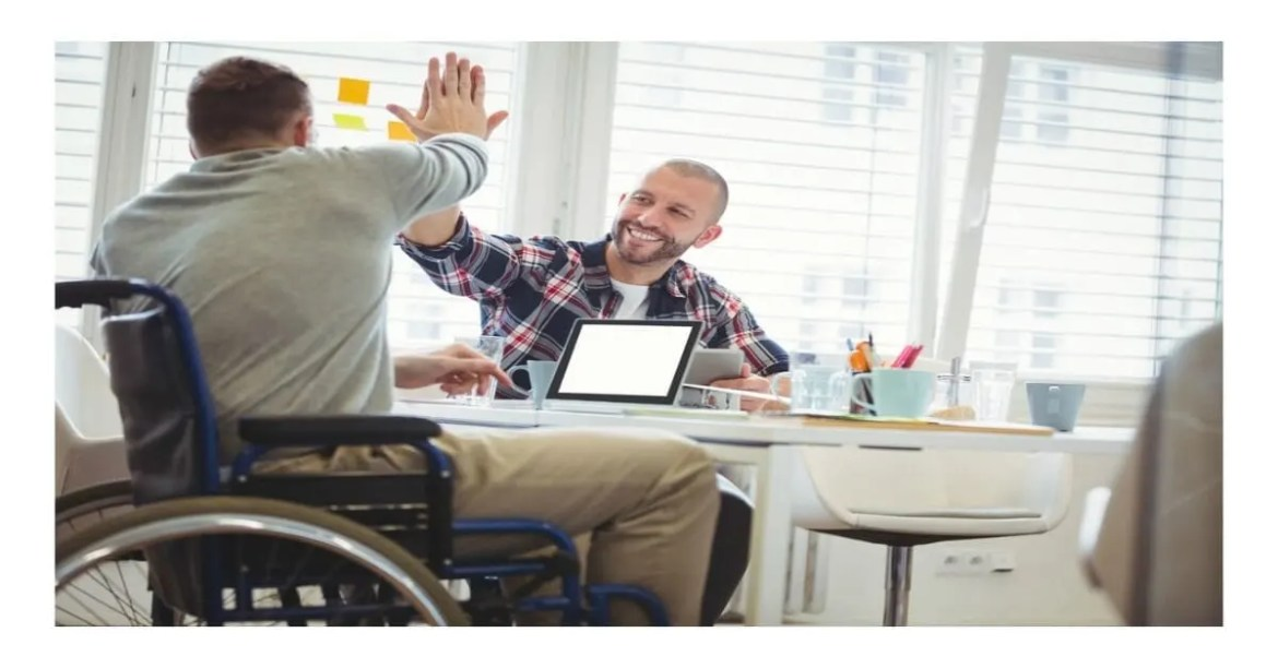 """disability ally - two men are seated, one in a wheelchair and the other on a chair, their hands are raised in a """"high five"""" salute"""