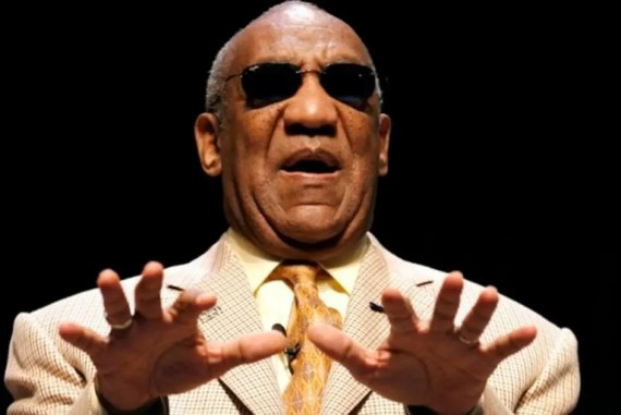"bill cosby blind - a man with dark brown skin and balding grey hair and black sunglasses is wearing a tan suit with dark orange tie, holding his hands forward as if he is using them to ""see"""