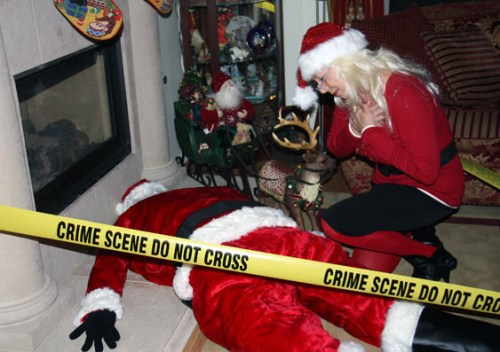 A photo of Linda in front of Santa at her Who Killed Santa party