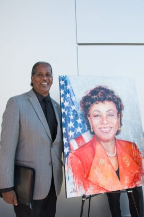 Romeo Garcia, director of Special Programs and Grants, poses next to the portrait painted by artist Nina Fabunmi.