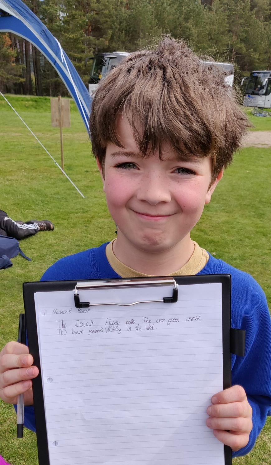 School boy shows his hand-written poem on a clipboard.
