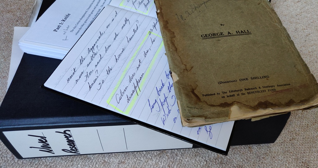 Folder, manuscript, notebook and old softbound book.
