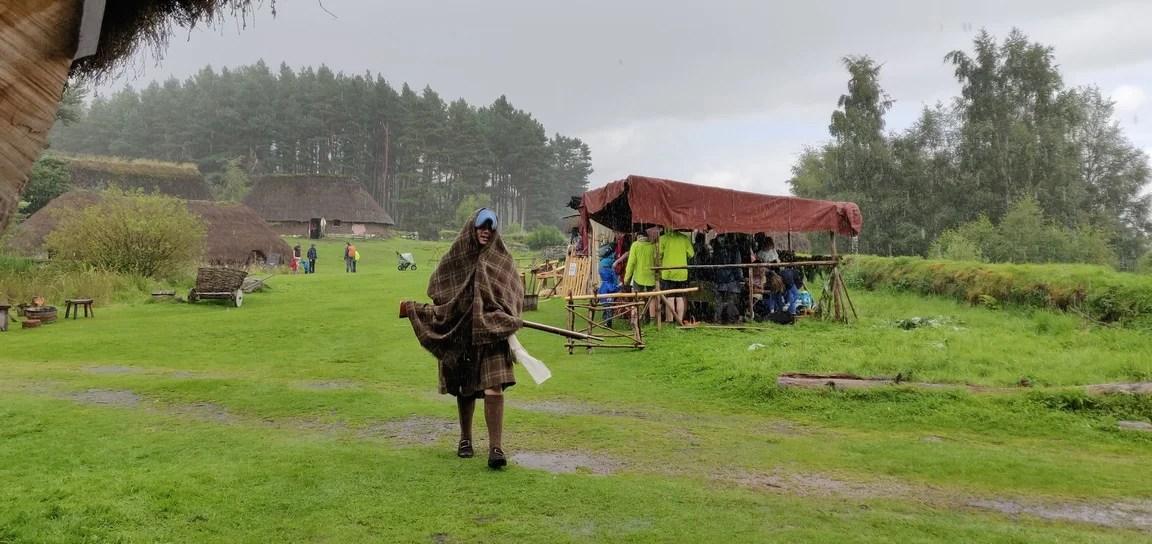 Man wrapped in plaid walks through the rain