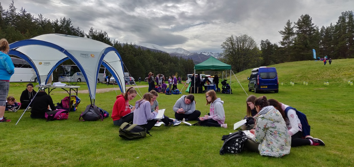 School pupils writing in outdoors with Cairngorms behind