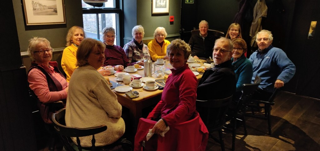 Group sitting around table having coffee and scones