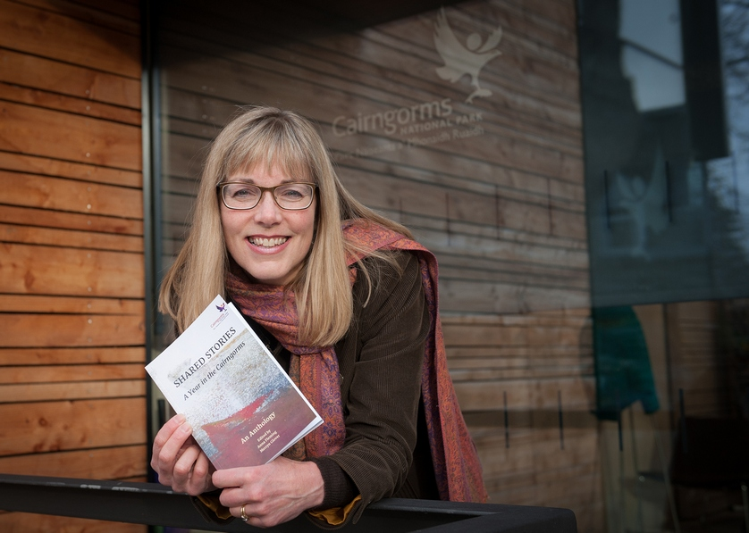 Merryn Glover holding copy of the Shared Stories: A Year in the Cairngorms anthology