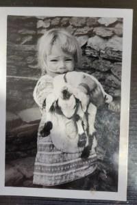 Little girl holding baby goat