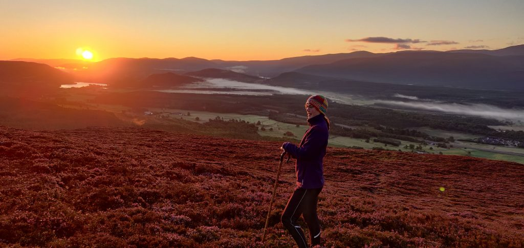 Merryn Glover on a heathery hill at sunrise with a shepherd's crook
