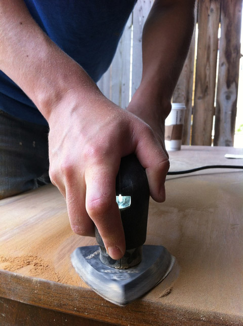 Sanding the topcoats off a wooden furniture.