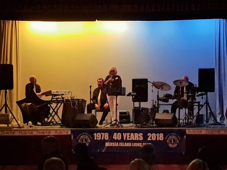 Sandra Bird Mersea Island Lions Club President welcomes guests to our Thank-you Evening. Also on stage are members of the band Rick and Us2 .