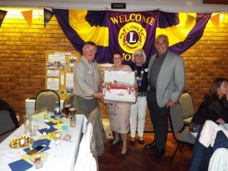 Club President Sandra Bird and Treasurer Keith Bird present prizes to lucky raffle winners.
