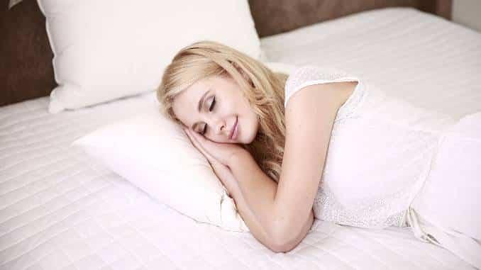 Mujer rubia durmiendo en una cama blanca.  Sonrisa en sus labios.