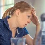 Mujer estresada en el trabajo.  Ella sostiene su frente, sentada frente a su trabajo en mano.