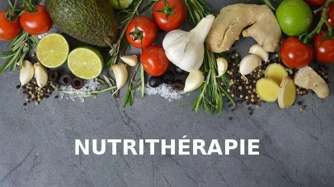 Nutritherapy escrito debajo de verduras y frutas sobre un fondo gris carbón.