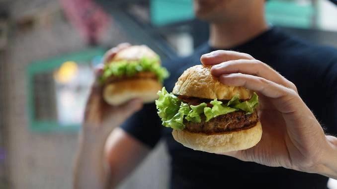 Hombre sujetando dos hamburguesas vegetarianas, una de las cuales está cerca en su mano