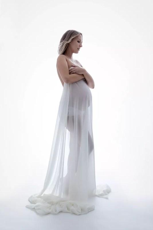photo de grossesse avec voilage blanc transparent sur fond blanc