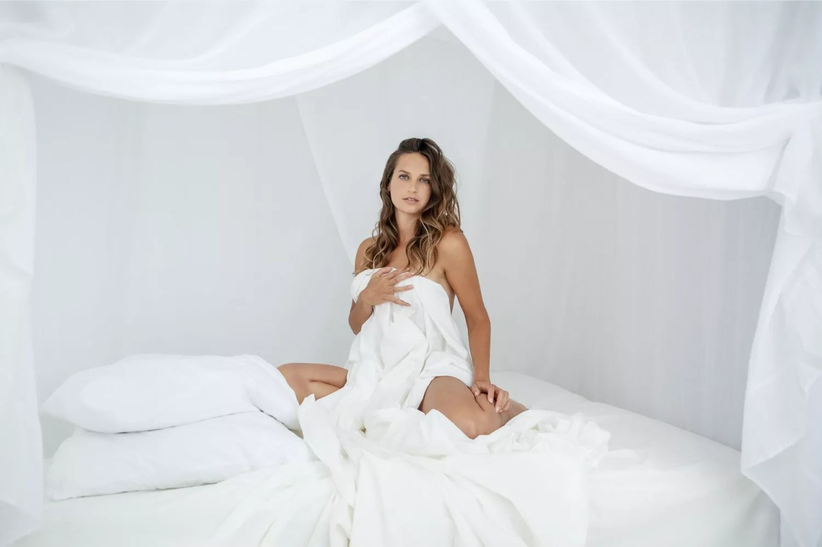 portrait femme dans lit à baldaquin séance photo boudoir juste un drap