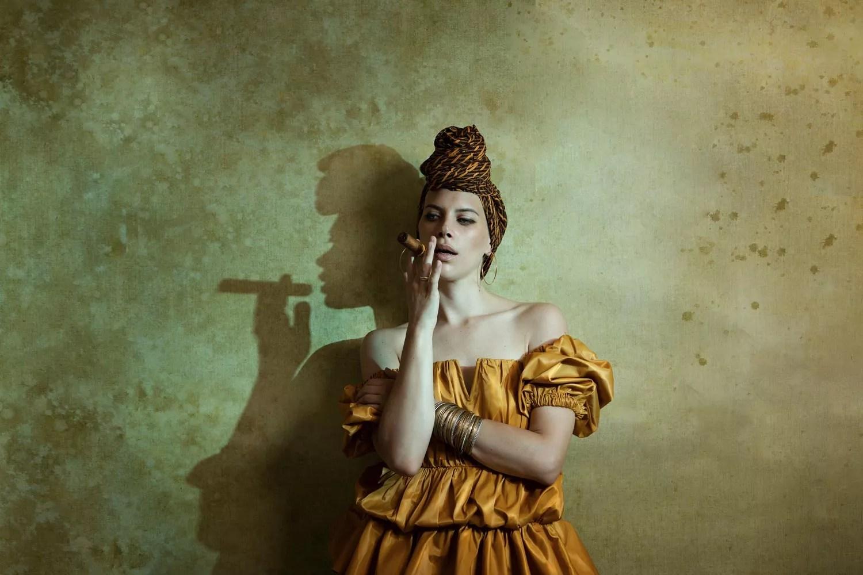shooting photo mode studio sur thème cuba femme avec cigare fond jaune peint à la main