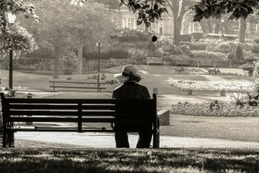 Grandma in hat sitting on a bench