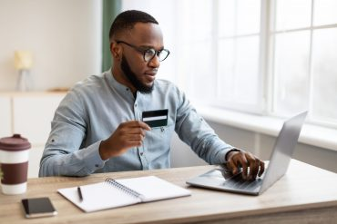 African American Businessman Using Credit Card And Laptop Shopping Online Sitting At Workplace In Modern Office. E-Commerce. Entrepreneur Making Payment Via Online Banking Service
