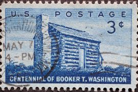 USA - Circa 1956 : a postage stamp printed in the US showing an antique log cabin with a chimney. Text: Centennial of Booker T. Washington
