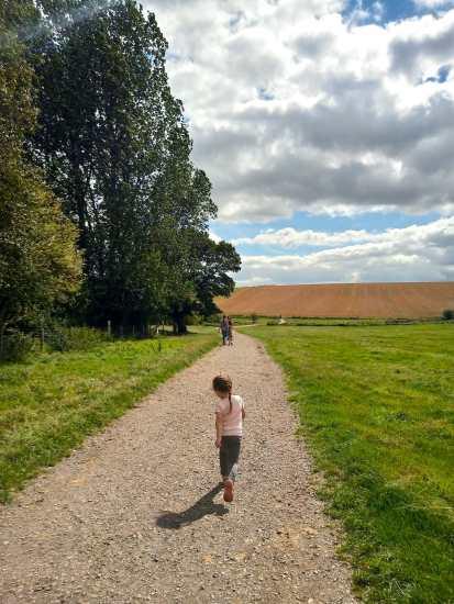 Small girl running along path in green field