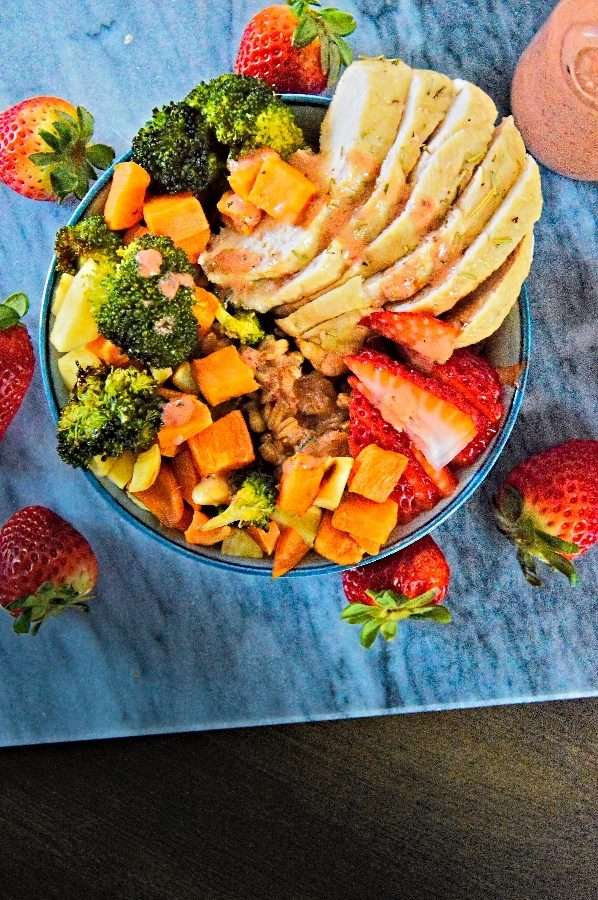 Grain bowl filled to the rim with chicken veggies and fruit on top of a bed of farro drizzled with strawberry balsamic dressing