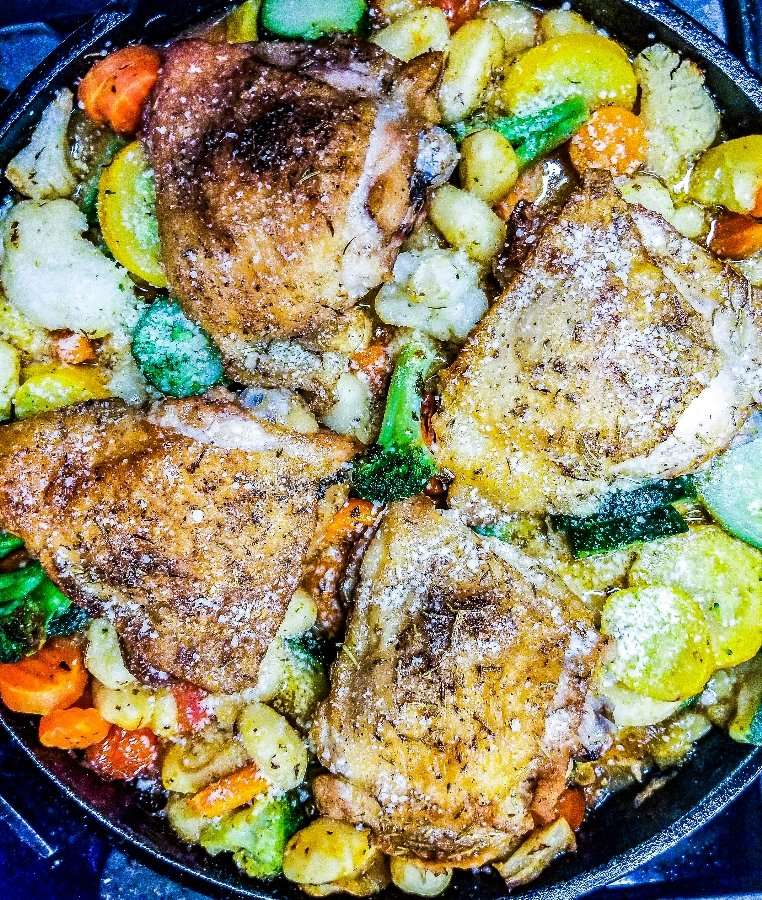 Overhead shot of the skillet loaded with gnocchi veggies and chicken with crispy skin.