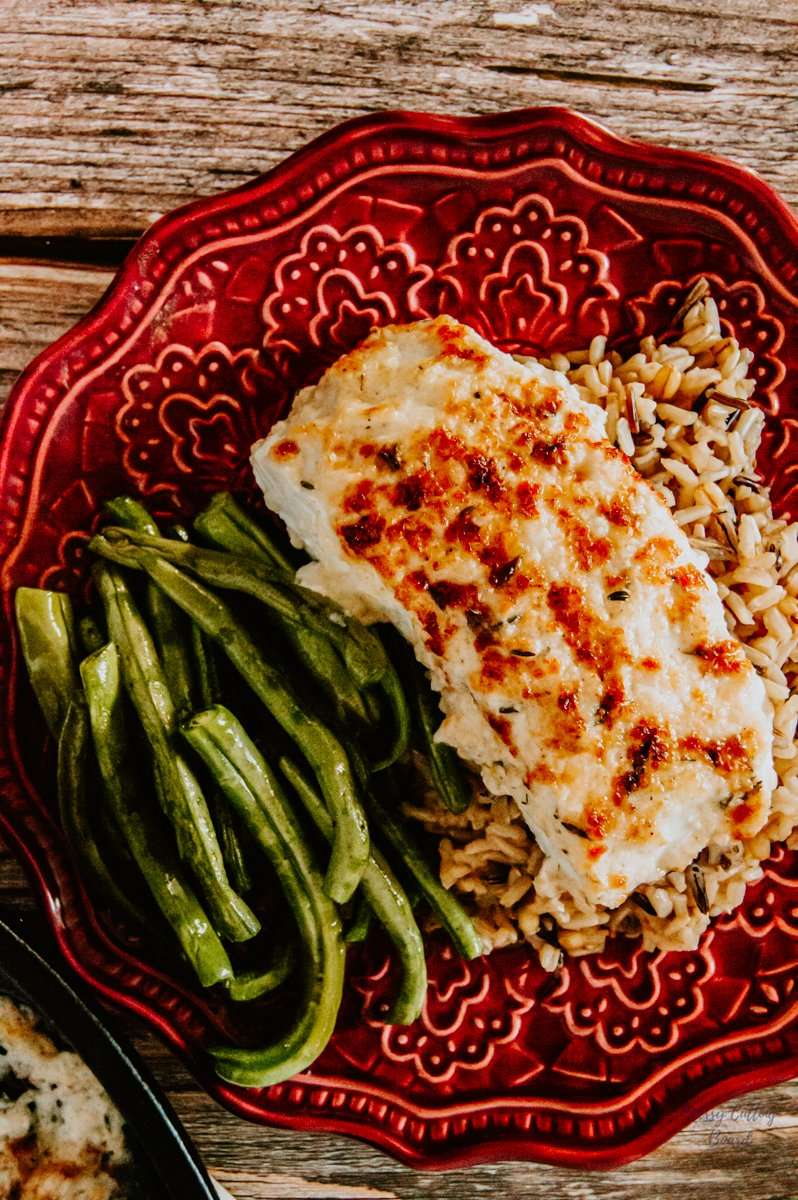 A plate served with Lemon-Herb Baked Halibut wild rice and fresh roasted green beans