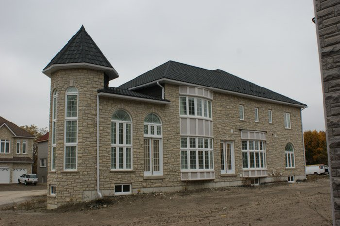 This beautiful fieldstone home in Ontario features a durable steel roof from Metal Roof Outlet - all it needs now is some nice landscaping to admire from those amazing windows!