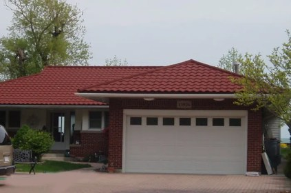 These Ontario homeowners are fond of red - so they topped their red-brick home with a complementary rust-coloured steel tile roof from Metal Roof Outlet.