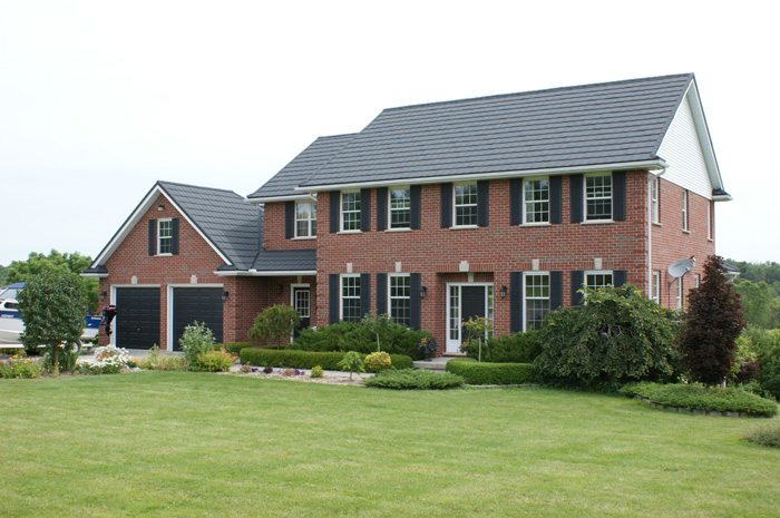 This beautiful two-story red brick home in Ontario features a slate-style steel roof from Metal Roof Outlet.