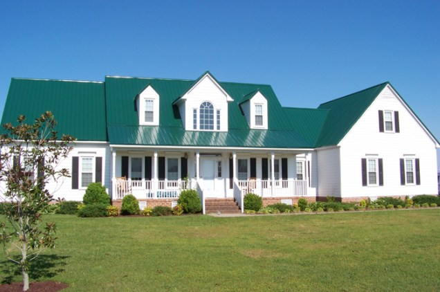 This beautiful white farmhouse features a dark green steel sheet roof from Metal Roof Outlet, Ontario.
