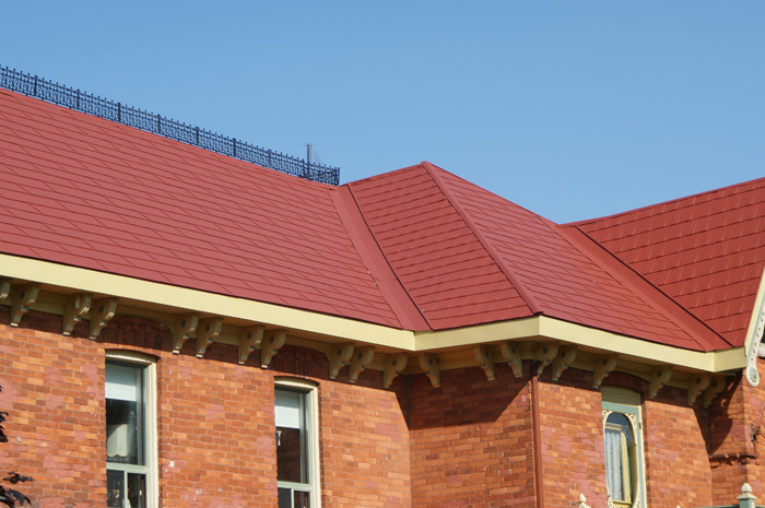 An orange brick house with a red metal shingle roof from Metal Roof Outlet