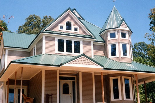 This peachy pink home completed its dollhouse look with scalloped siding, turrets, and a lovely teal steel sheet roof from Metal Roof Outlet.