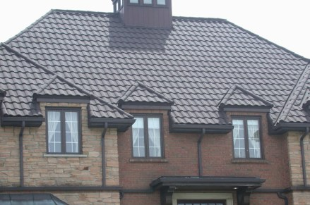 The classic stone and brick of this Ontario building is complemented by a dark brown metal tile by Metal Roof Outlet.