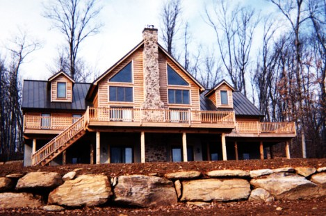 This cottage-style wood home in Ontario features tons of beautiful windows and a stone chimney, all of it topped off with a black steel sheet roof from Metal Roof Outlet.
