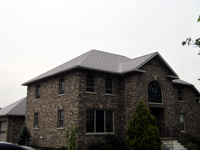 The pebbly brickwork of this gorgeous two-story Ontario home is complemented by a sleek Steel Wakefield Bridge Shingle by Metal Roof Outlet.