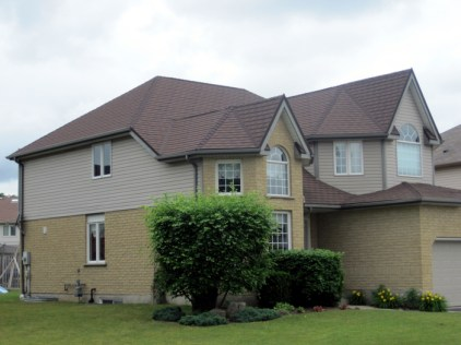 This two-story, multi-tiered home features a steel shingle in Heather Blend by Metal Roof Outlet, Ontario.