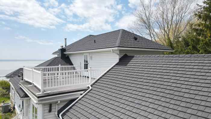 Close-up view of charcoal metal roof on a white cottage with a lake and trees in the background. Cottage located in Port Stanley, Ontario with Tilcor CF Shingle metal roof by metalroofoutlet.com