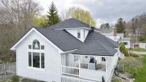 White cottage with grey metal roof from Metal Roof Outlet with trees and cottages in the background