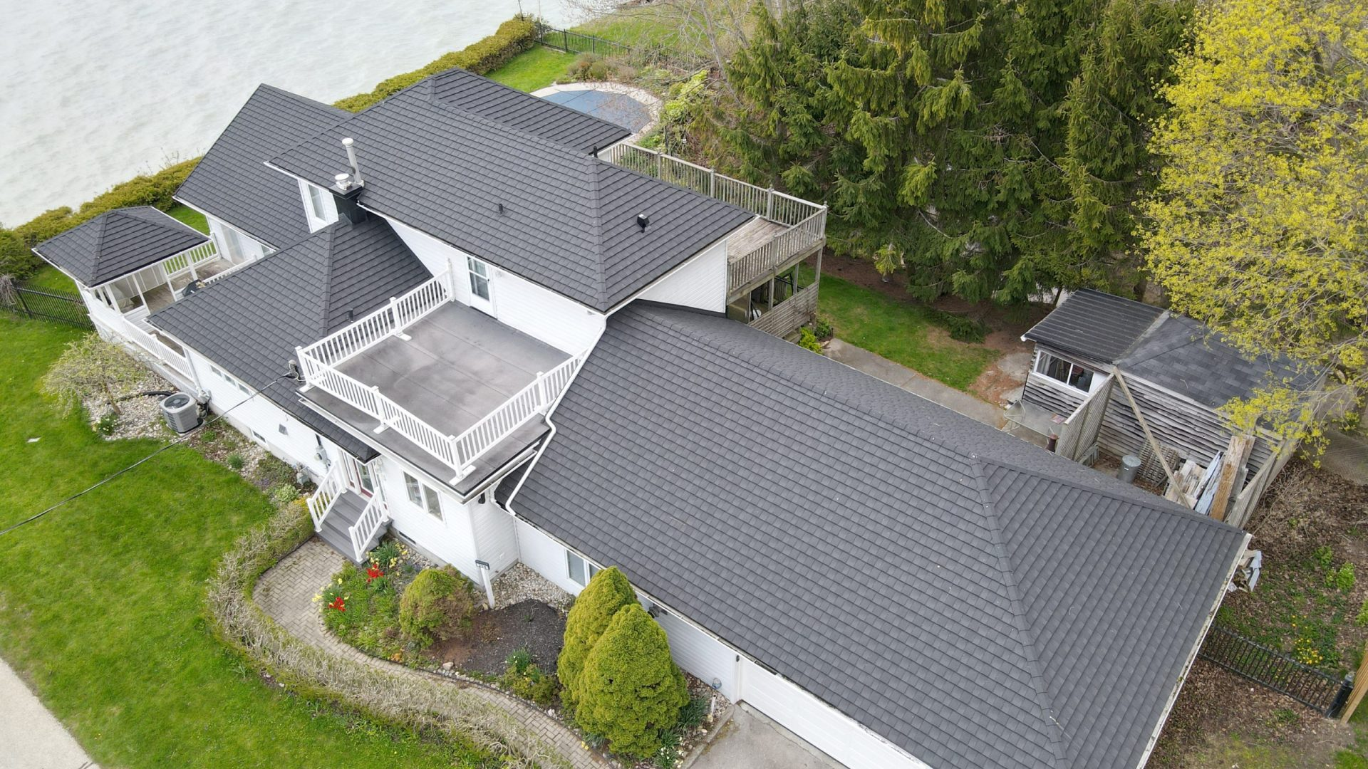 Aerial view of grey metal shingles from metal roof outlet on a white home with trees and shrubs surrounding