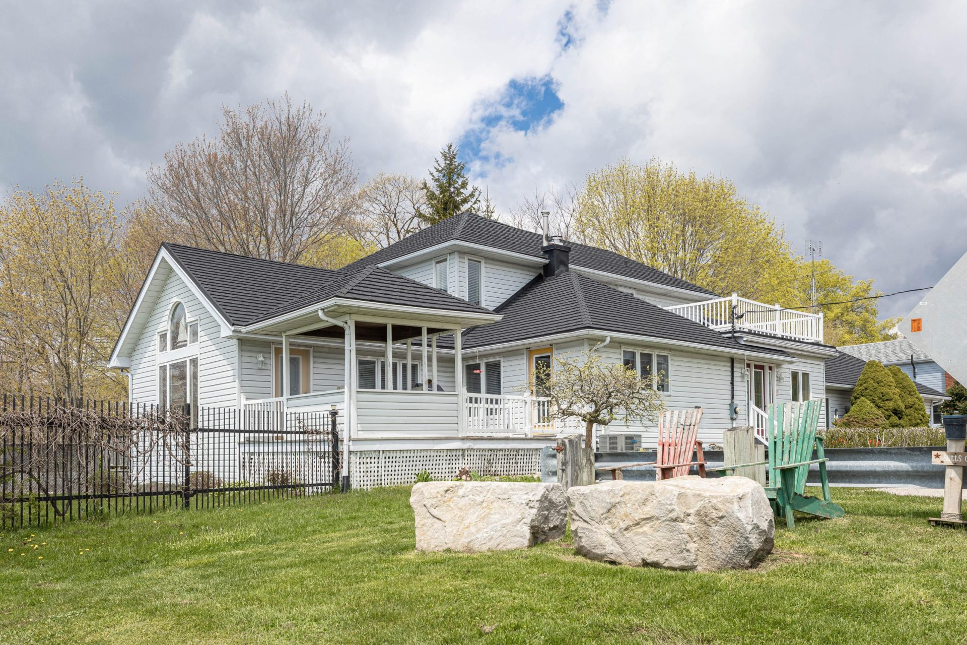 White house with grey metal roof from Metal Roof Outlet and green lawn with a single tree, large decorative rocks and a fence with muskoka chairs on the lawn