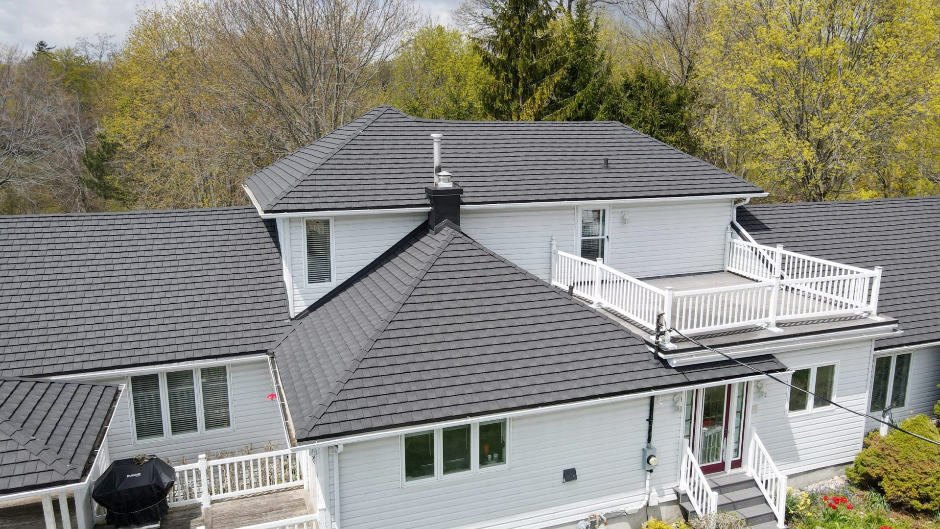 Grey metal shingles from metal roof outlet on a white home with trees and shrubs surrounding