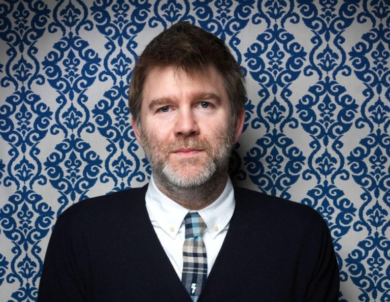 james murphy in front of blue wallpaper